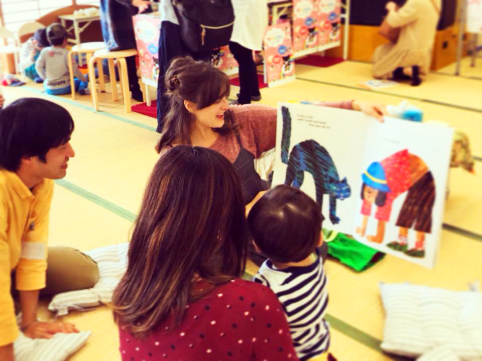 English Teacher reading a book to children on tatami mat